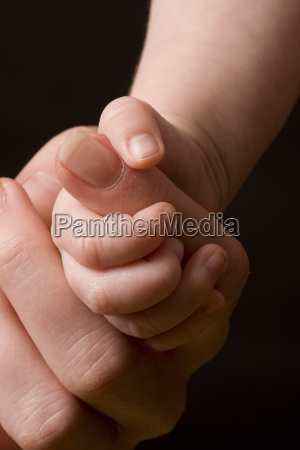 babys hand gripping adult finger