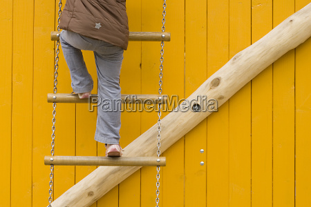 rope ladder against yellow wooden wall