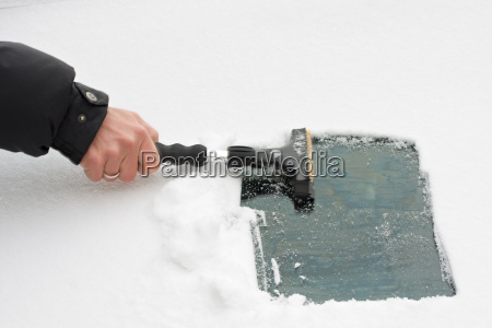 hand with an ice scraper