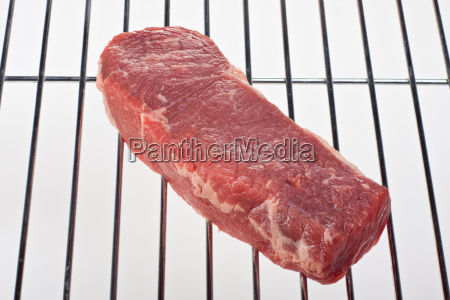 raw steak on a grill isolated