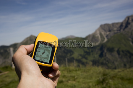 hand with gps receiver and mountains