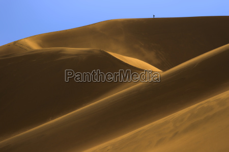 tiny backpacker in dunes