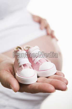 pregnant woman holding pink shoes