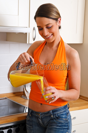 young woman is pouring herself orange
