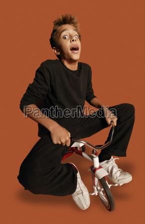 teenage boy on tiny bicycle