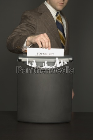 businessman shredding document