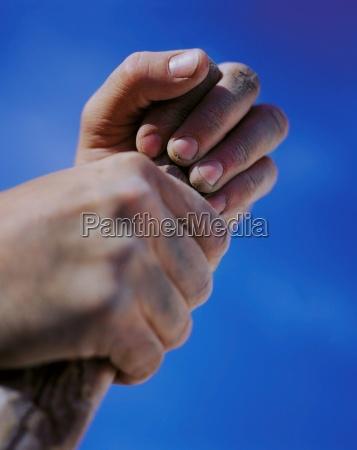 hands holding stick against blue sky