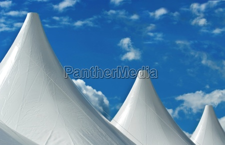 tent roofs protrude into the cloudy