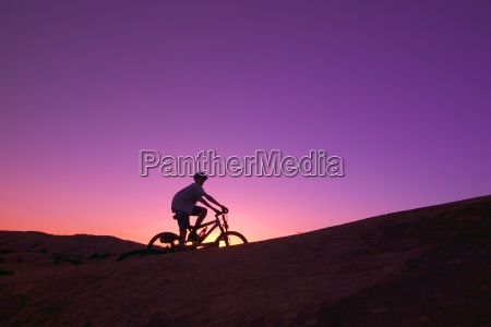 person on bike at sunset