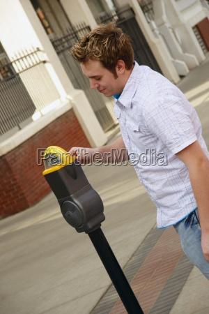 man plugging a parking meter