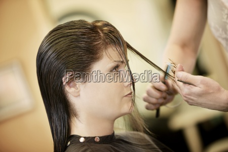 woman having her hair cut
