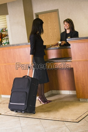 woman checking in at hotel lobby
