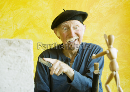 crazy artist with a wooden figure