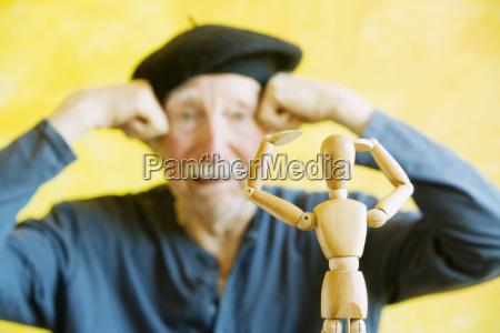 artist mimics a wooden figure