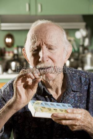 elder, man, with, a, pill, case - 2202411