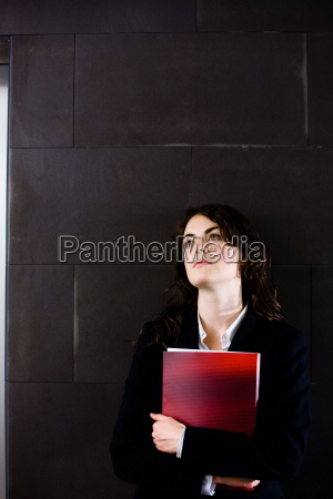 young businesswoman in dark suit holding