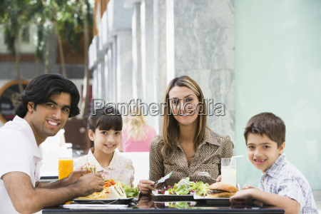 family at restaurant eating and smiling