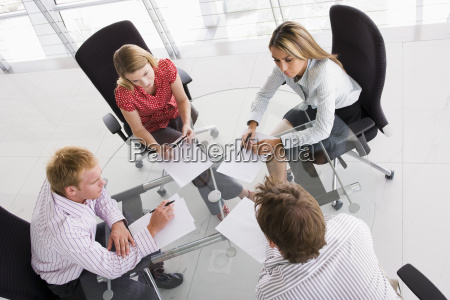 four businesspeople in a boardroom with