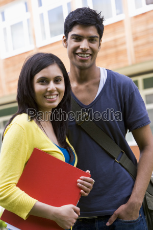 two students standing outdoors smiling