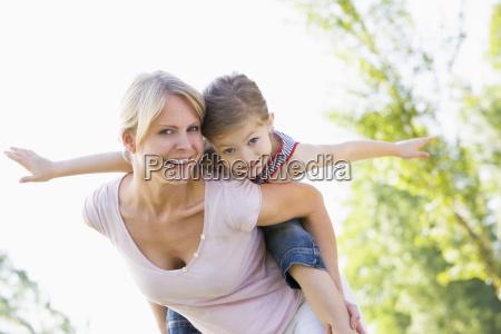 woman giving young girl piggyback ride