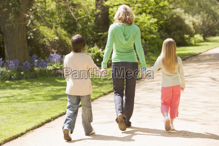 mother and two young children walking
