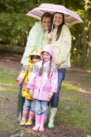 family outdoors in rain with umbrella