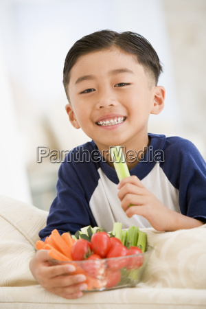 young boy eating bowl of vegetables