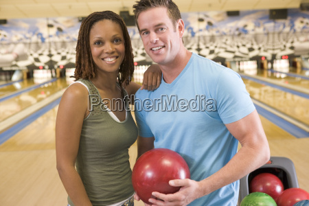 couple in bowling alley holding ball