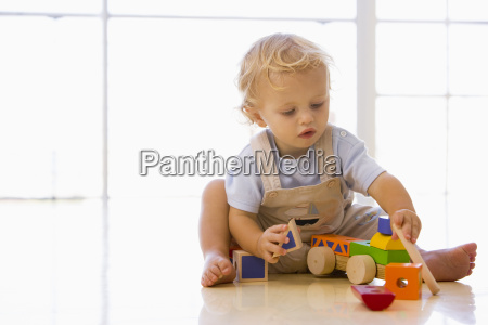 baby indoors playing with toy truck