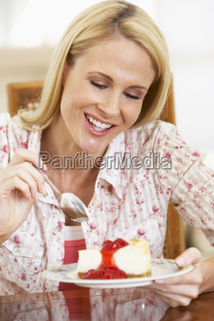 mid adult woman eating cheesecake