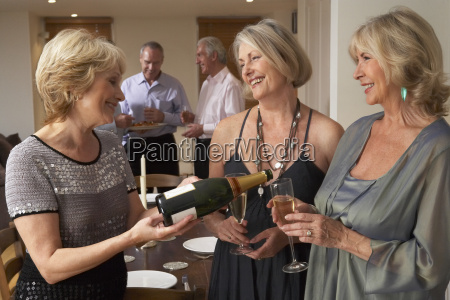 woman serving champagne to her guests
