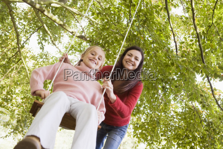 woman outdoors pushing young girl on