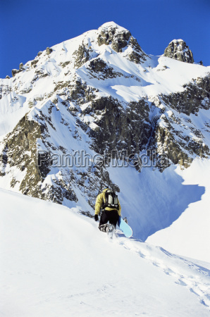 snowboarder going up hill carrying board