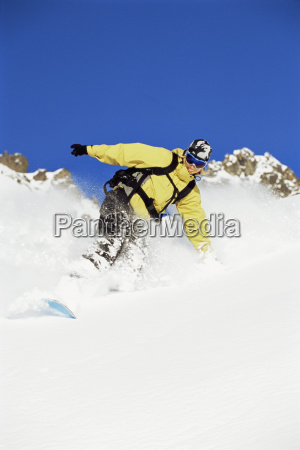 snowboarder coming down hill smiling