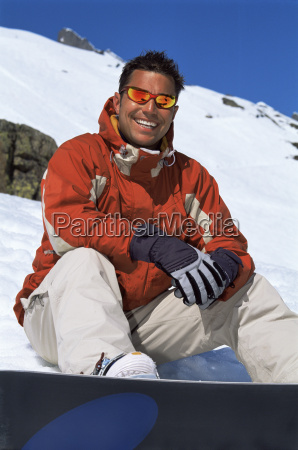 snowboarder sitting on hill with board