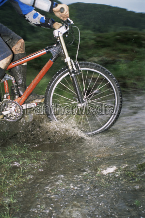man outdoors on trails riding bicycle