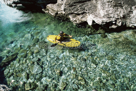kayaker in calm water near large