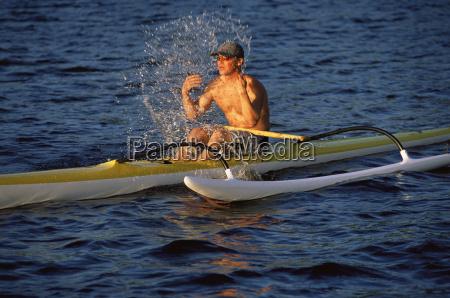 kayaker outdoors splashing water on face