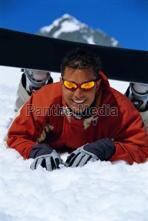 snowboarder lying on snowy hill wearing