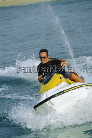 man jet skiing and smiling selective