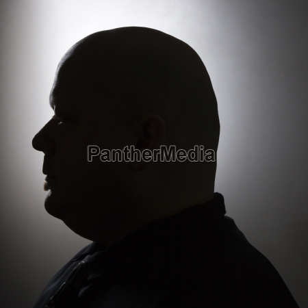 silhouette of bald man
