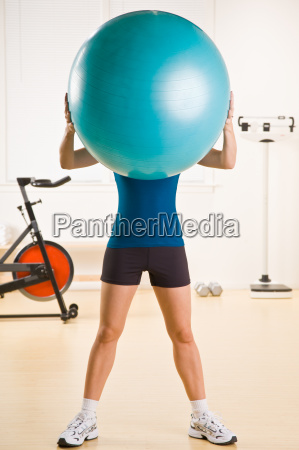 woman holding exercise ball in health
