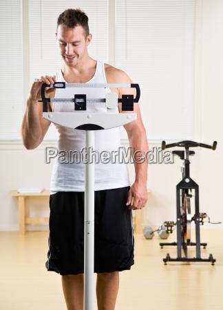 man weighing himself in health club