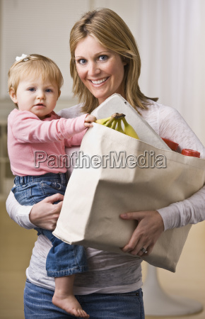 mother holding daughter and groceries