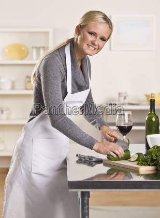 attractive woman slicing cucumber