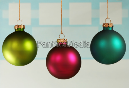 three colorful ornaments on light blue