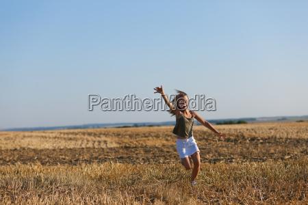 girl runs on autumnal field