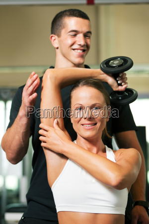 trainer and woman in gym