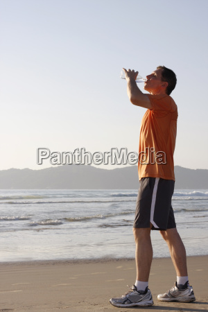 jogger drinking from water bottle