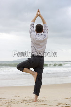 manager doing yoga on beach